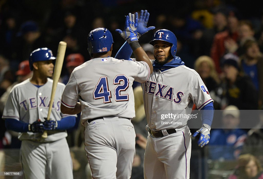 <a gi-track='captionPersonalityLinkClicked' href=/galleries/search?phrase=Elvis+Andrus&family=editorial&specificpeople=4845974 ng-click='$event.stopPropagation()'>Elvis Andrus</a> of the Texas Rangers (R) high-fives teammate <a gi-track='captionPersonalityLinkClicked' href=/galleries/search?phrase=Adrian+Beltre&family=editorial&specificpeople=202631 ng-click='$event.stopPropagation()'>Adrian Beltre</a> after Beltre hit a two-run home run scoring Andrus during the eighth inning against the Chicago Cubs at Wrigley Field on April 16, 2013 in Chicago, Illinois. All uniformed team members are wearing jersey number 42 in honor of Jackie Robinson Day.