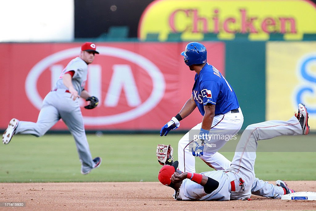 <a gi-track='captionPersonalityLinkClicked' href=/galleries/search?phrase=Elvis+Andrus&family=editorial&specificpeople=4845974 ng-click='$event.stopPropagation()'>Elvis Andrus</a> #1 of the Texas Rangers looks on as <a gi-track='captionPersonalityLinkClicked' href=/galleries/search?phrase=Zack+Cozart&family=editorial&specificpeople=6889199 ng-click='$event.stopPropagation()'>Zack Cozart</a> #2 of the Cincinnati Reds chases down a missed throw to second baseman Brandon Phillips #4 of the Cincinnati Reds at Rangers Ballpark in Arlington on June 28, 2013 in Arlington, Texas.