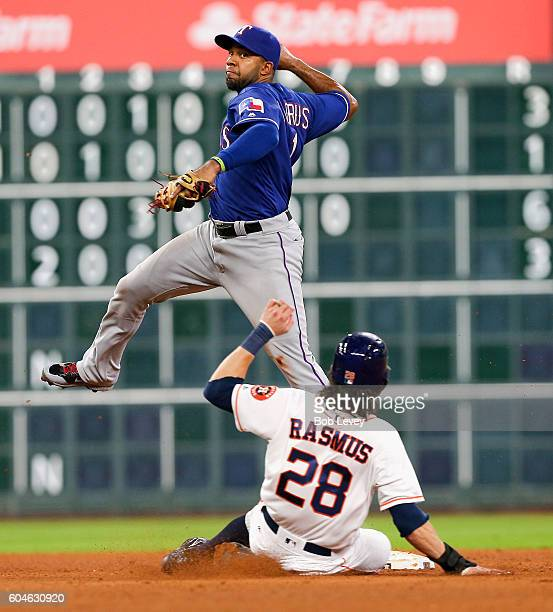Elvis Andrus of the Texas Rangers makes a leaping throw as he forces Colby Rasmus of the Houston Astros at second base and throws to first base to...