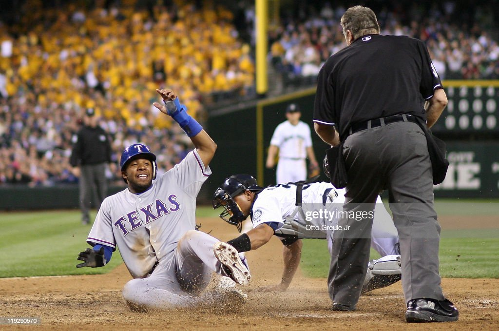 <a gi-track='captionPersonalityLinkClicked' href=/galleries/search?phrase=Elvis+Andrus&family=editorial&specificpeople=4845974 ng-click='$event.stopPropagation()'>Elvis Andrus</a> #1 of the Texas Rangers scores against catcher <a gi-track='captionPersonalityLinkClicked' href=/galleries/search?phrase=Miguel+Olivo&family=editorial&specificpeople=209185 ng-click='$event.stopPropagation()'>Miguel Olivo</a> #30 of the Seattle Mariners on a groundout by Josh Hamilton #32 in the eighth inning at Safeco Field on July 16, 2011 in Seattle, Washington.