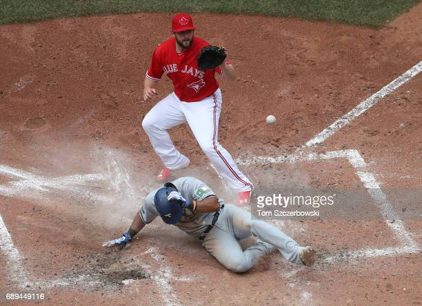 Elvis Andrus of the Texas Rangers scores on a wild pitch as Dominic Leone of the Toronto Blue Jays covers home plate in the seventh inning during MLB...