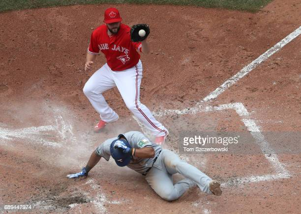 Elvis Andrus of the Texas Rangers slides across home plate as he scores on a wild pitch as Dominic Leone of the Toronto Blue Jays covers home plate...
