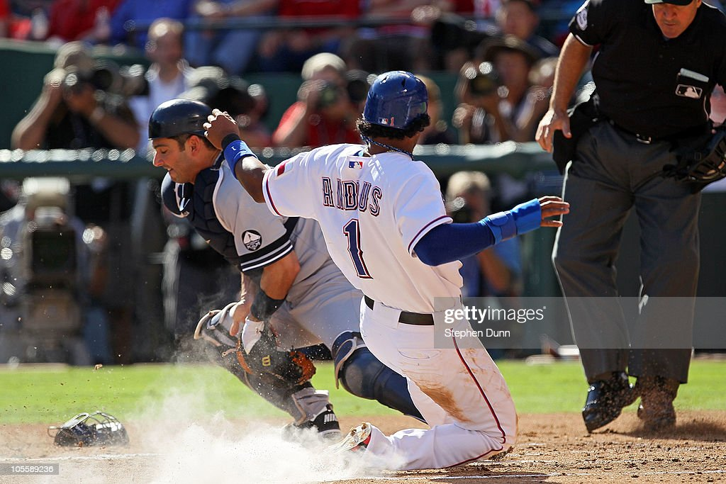 Elvis Andrus of the Texas Rangers slides into home plate to score on a double steal in the bottom of the first inning against Jorge Posada of the New...