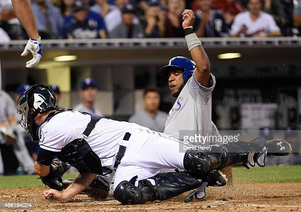 Elvis Andrus of the Texas Rangers steals home ahead of the tag of Austin Hedges of the San Diego Padres during the seventh inning of a baseball game...