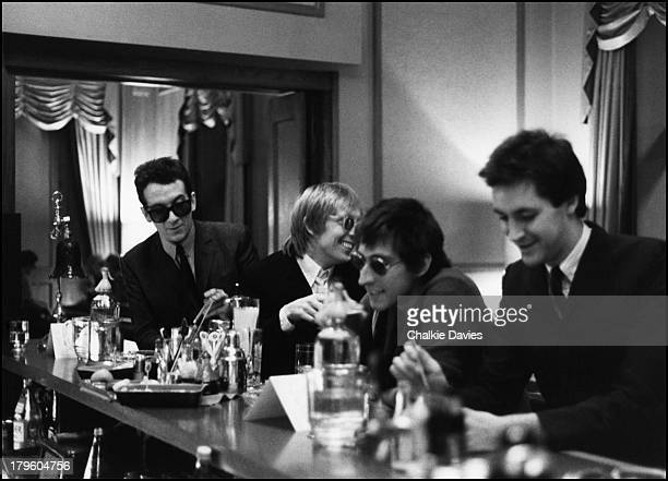 Elvis Costello and the Attractions sit at a bar in Jersey during the making of a video for 'New Lace Sleeves' from the LP 'Trust' 1981 Left to right...