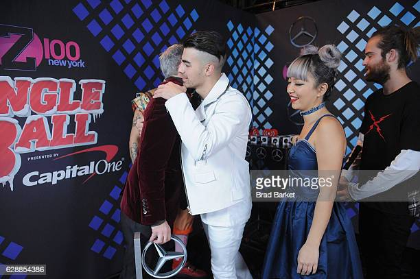 Elvis Duran speaks with Joe Jonas JinJoo Lee and Jack Lawless of DNCE in the broadcast room at the Z100's Jingle Ball 2016 at Madison Square Garden...