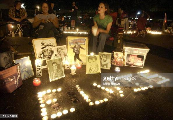 Elvis fans sit by a shrine to Elvis Presley they made during the candle light vigil August 15 2004 at Graceland in Memphis Tennessee The vigil is the...