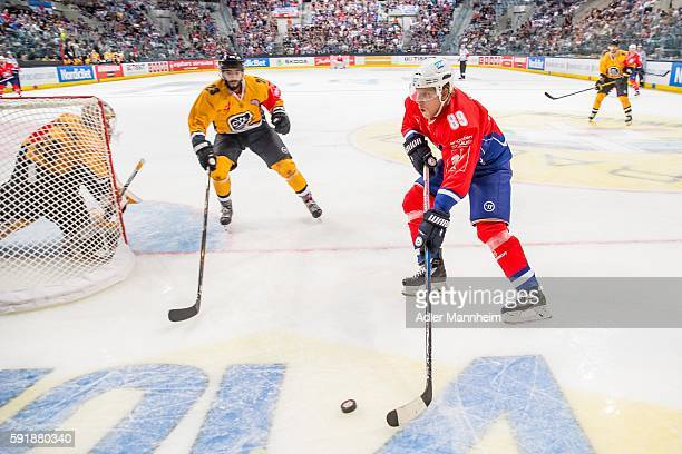 Elvis Merzlikins and Giovanni Morini of HCL battles David Wolf of Adler during the Champions Hockey League match between Adler Mannheim and HC Lugano...