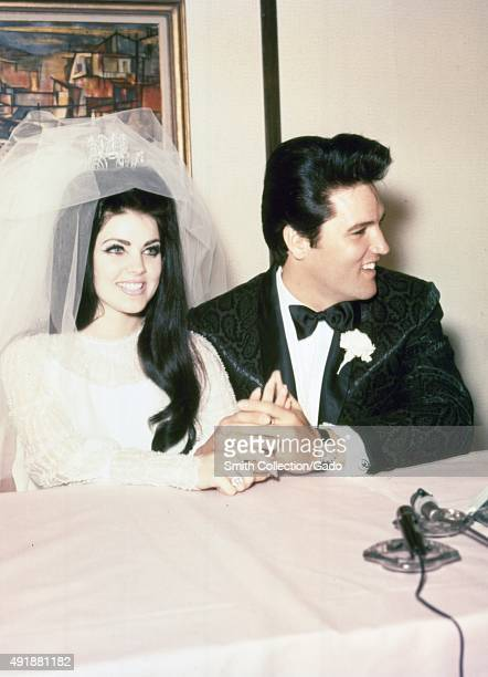 Elvis Presley and Priscilla Presley wedding photo wearing tuxedo and wedding dress smiling and holding hands during a press conference following...