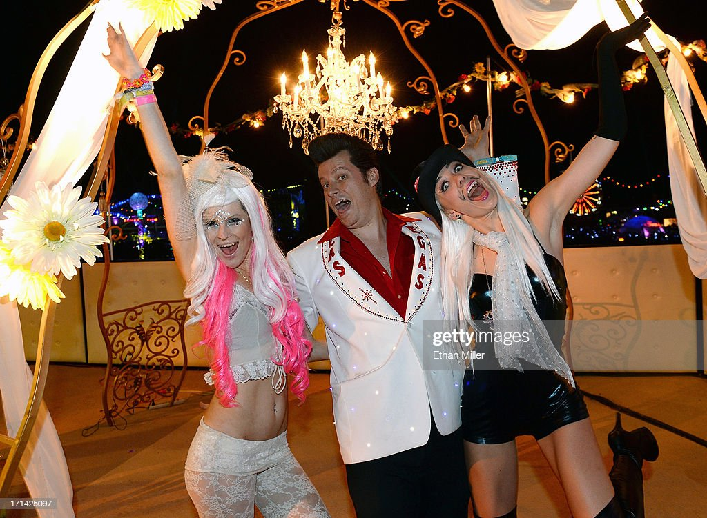 Elvis Presley impersonator Brian Mills (C) poses with Jessica O'Donnell (L) and Adele Vannini (R) after he performed their commitment ceremony at the 17th annual Electric Daisy Carnival at Las Vegas Motor Speedway on June 23, 2013 in Las Vegas, Nevada.
