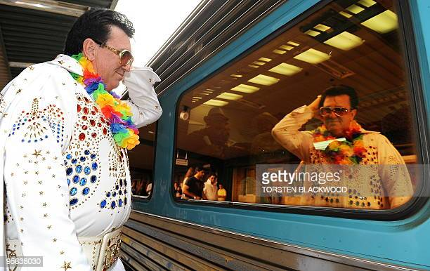 Elvis Presley impersonator Graeme MacKaway checks his hair in the window of the 'Elvis Express' before boarding at Central Station in Sydney on...