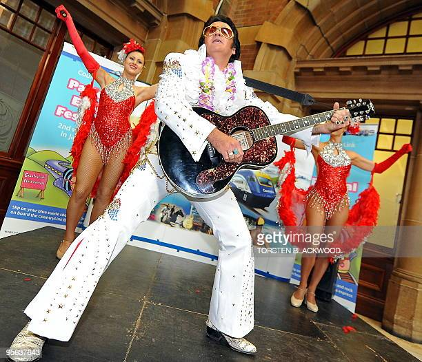 Elvis Presley impersonator Scott Crawford plays his guitar before boarding the 'Elvis Express' at Central Station in Sydney on January 8 for the 18th...
