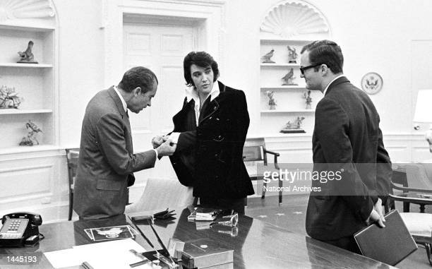 Elvis Presley shows President Richard Nixon his cuff links December 21 1970 at the White House