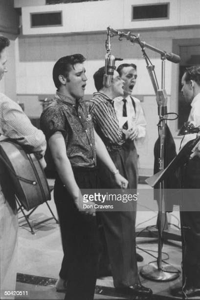 Elvis Presley singing expressively while recording a new song in a recording studio backed up by the Jordanaires made up of Gordon Stoker Neal...