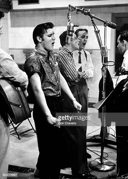 Elvis Presley singing expressively while recording a new song in an unident recording studio backed up by the Jordanaires