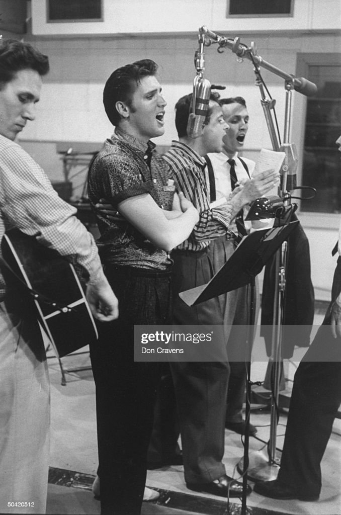 Elvis Presley singing expressively with arms folded while recording a new song in an unidentified recording studio, backed up by the Jordanaires, made up of Gordon Stoker, Neal Matthews Jr., Hoyt Hawkins and Hugh Jarrett.