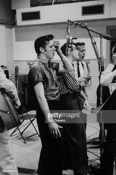 Elvis Presley singing expressively with hand to forehead while recording a new song in an unidentified recording studio backed up by the Jordanaires...
