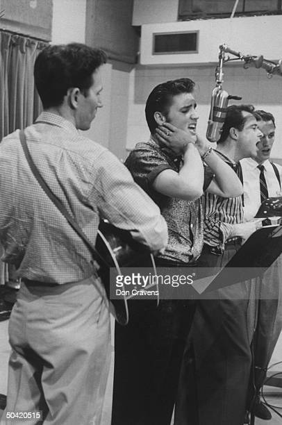 Elvis Presley singing expressively with hands to face while recording a new song in an unidentified recording studio backed up by the Jordanaires...