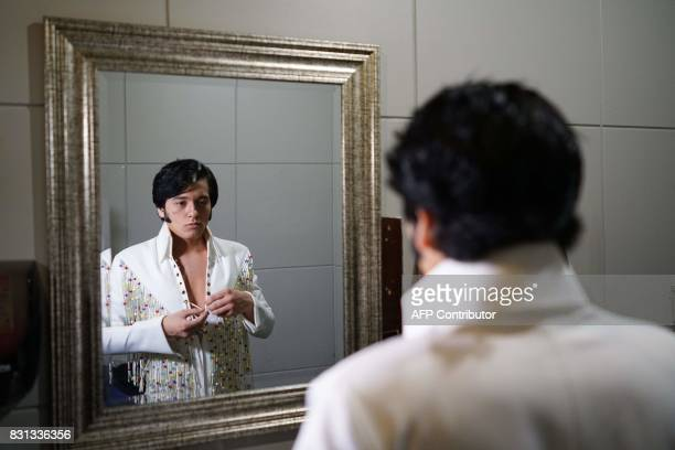 Elvis tribute artist Matthew Boyce checks his appearance in a mirror backstage before taking part in the preliminary round of the 'Images of the...