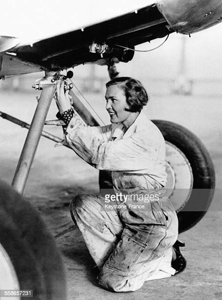 Elvy Kalep jeune fille qui espere participer prochainement au vol Transoceanique avec Roger Williams photographiee a l'aeroport bricolant l'avion qui...