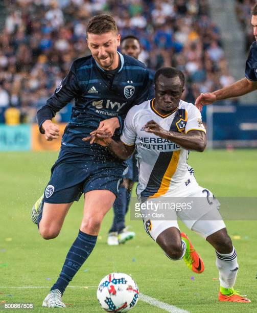 Ema Boateng of Los Angeles Galaxy with the ball as Ilie Sanchez of Sporting Kansas City defends during the Los Angeles Galaxy's MLS match against...
