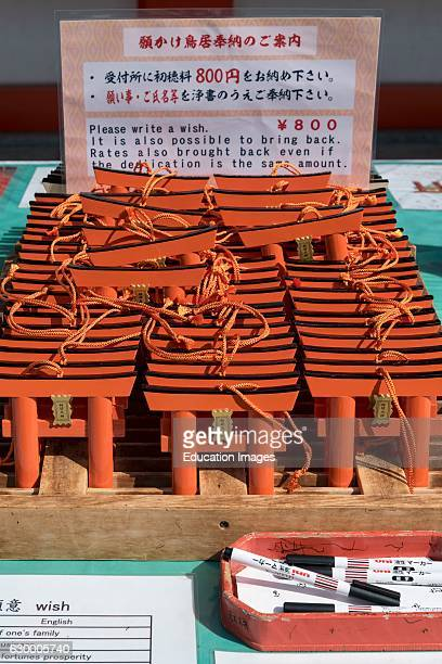 Ema wish plaques in the shape of orange torii gate at Fushimi Inaritaisha Shrine Kyoto Japan