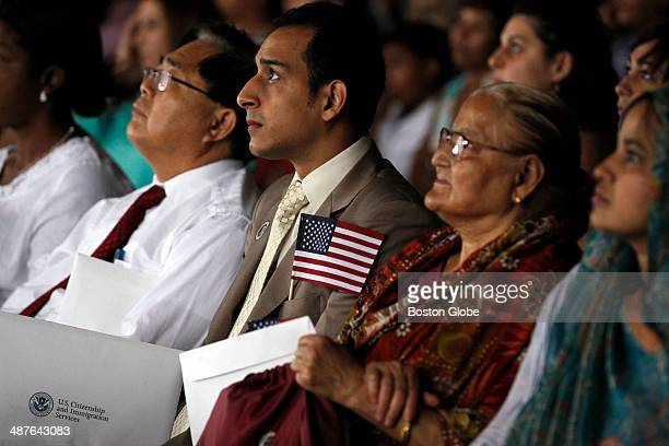 Emad Mesdary originally of Egypt center looks up at the screen as Momtaz Begum originally of Bangladesh second from right sits beside him as the two...