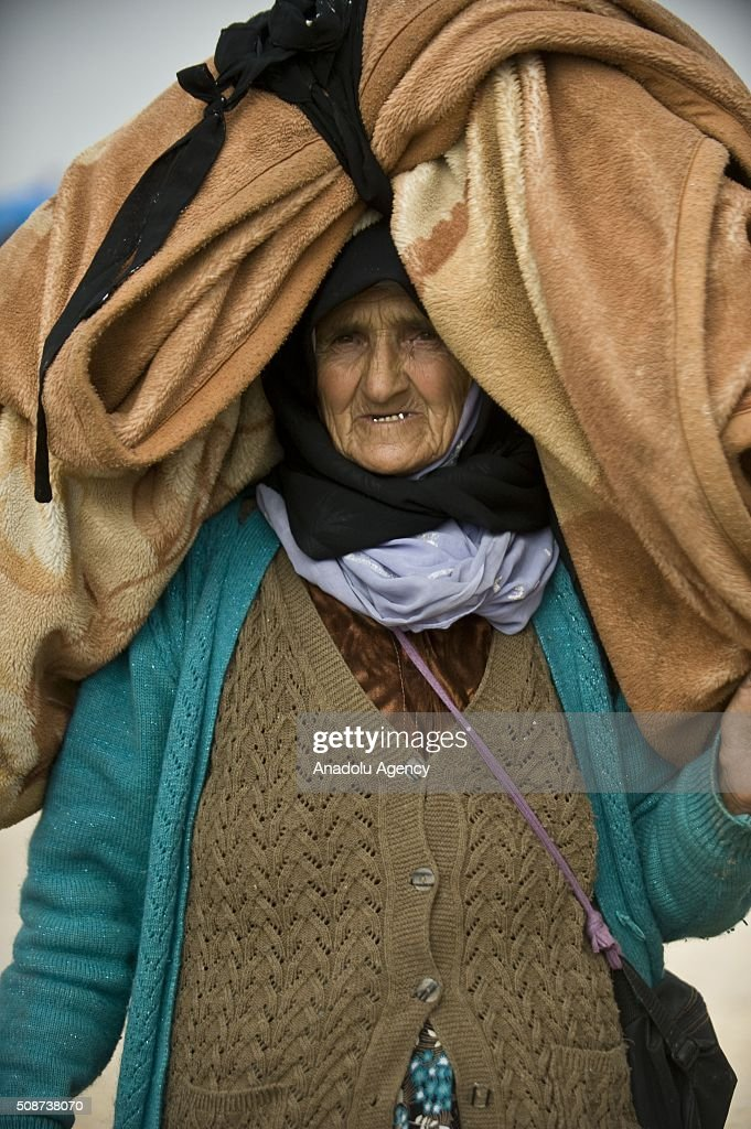 Eman Ali, 74, a Syrian woman who fled bombing in Aleppo, carries her belongings on her head at the Oncupinar crossing, opposite the Turkish province of Kilis, near Azaz town of Aleppo, Syria on February 6, 2016. Thousands of Syrians have massed on the Syrian side of the border seeking refuge in Turkey.