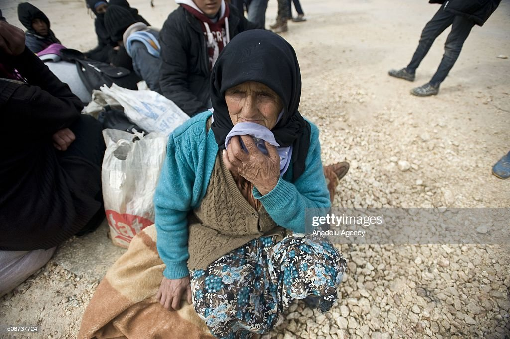 Eman Ali, 74, a Syrian woman who fled bombing in Aleppo, sits on her belongings as she waits at the Oncupinar crossing, opposite the Turkish province of Kilis, near Azaz town of Aleppo, Syria on February 6, 2016. Thousands of Syrians have massed on the Syrian side of the border seeking refuge in Turkey.