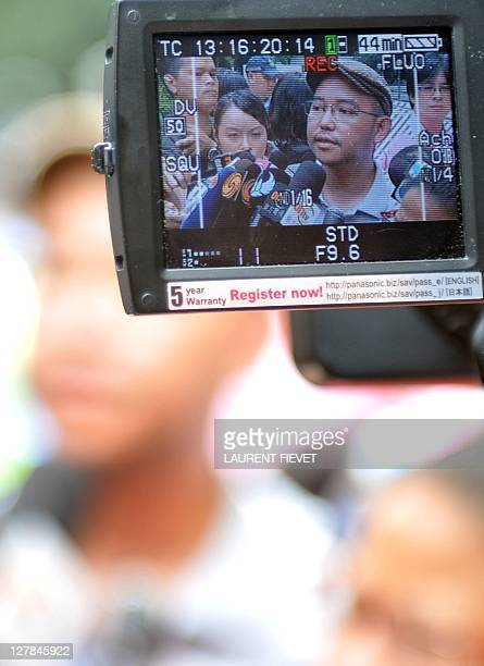 Eman Villanueva vice chairman of the Filipino Migrant Workers' Union is seen through a camera man's video recorder talking to the media after...