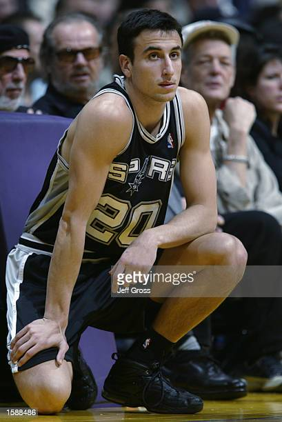 Emanuel Ginobili of the San Antonio Spurs kneels at the scorer's table during the NBA season opener against the Los Angeles Lakers at Staples Center...