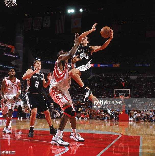 Emanuel Ginobili of the San Antonio Spurs makes a layup against Dikembe Mutombo of the Houston Rockets at Toyota Center on December 9 2004 in Houston...