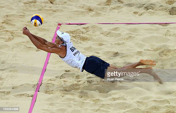 Emanuel Rego of Brazil dives to attempt to hit a return against Jonas Reckermann and Julius Brink of Germany during the Men's Beach Volleyball Gold...