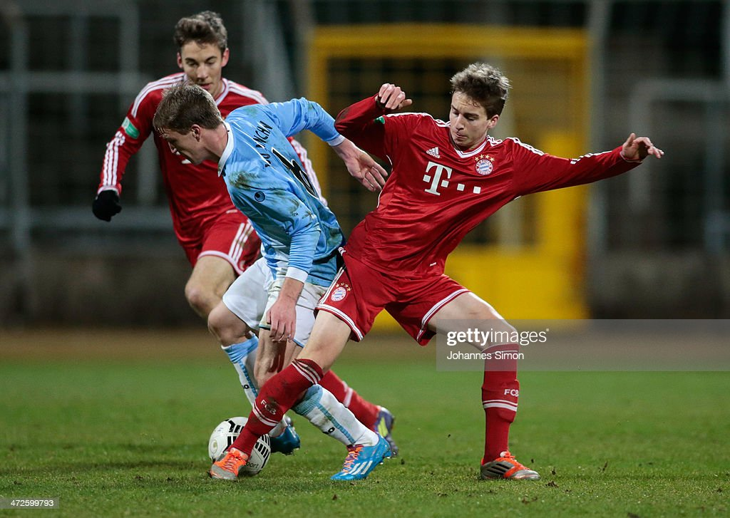 Emanuel Taffertshofer (C) of 1860 Muenchen battles for the ball with Michael Eberwein (L) and Gianluca Gaudino (R) of FC Bayern during the A Juniors Bundesliga match between 1860 Muenchen and Bayern Muenchen at Stadion an der Gruenwalder Strasse on February 21, 2014 in Munich, Germany.
