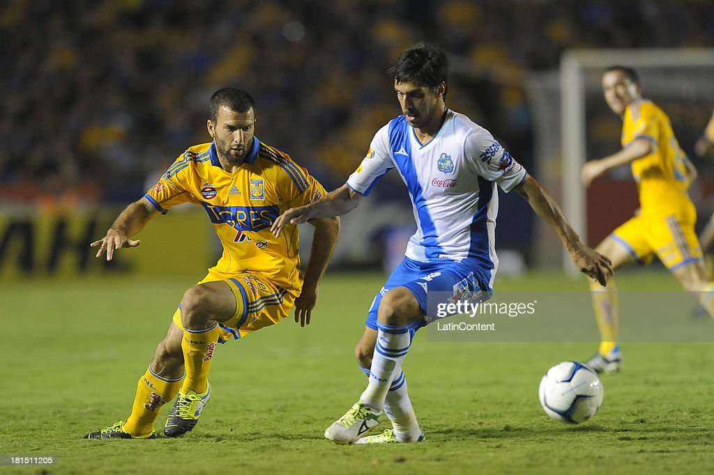 <a gi-track='captionPersonalityLinkClicked' href=/galleries/search?phrase=Emanuel+Villa&family=editorial&specificpeople=3061294 ng-click='$event.stopPropagation()'>Emanuel Villa</a> of Tigres competes for the ball during a match between Tigres UANL and Puebla FC as part of the Liga MX at Universitario stadium on September 21, 2013 in Monterrey, Mexico.
