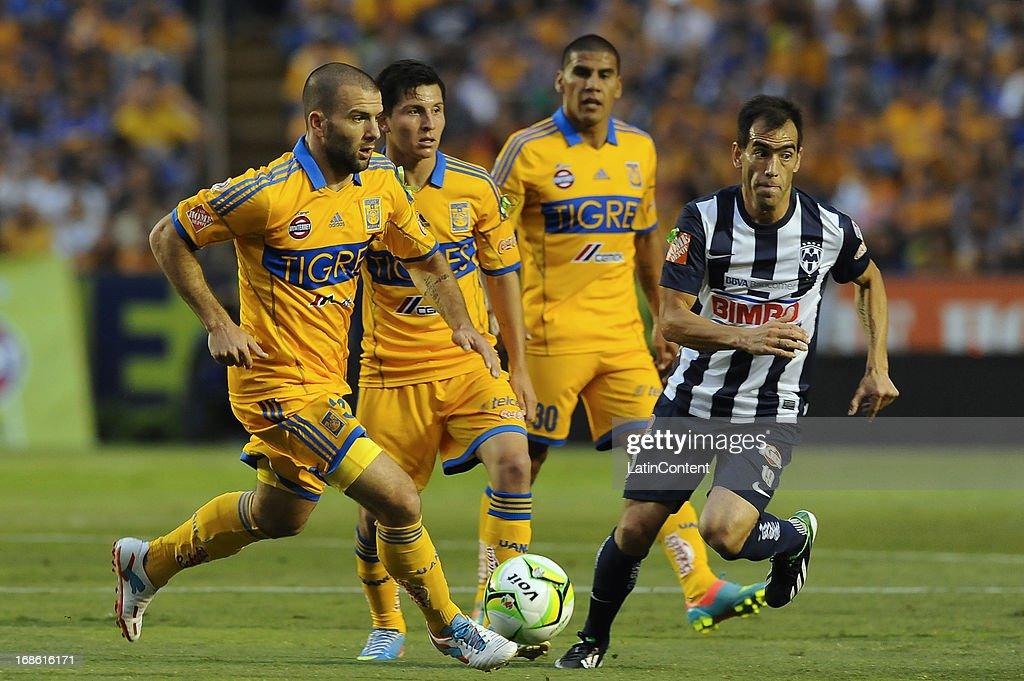 <a gi-track='captionPersonalityLinkClicked' href=/galleries/search?phrase=Emanuel+Villa&family=editorial&specificpeople=3061294 ng-click='$event.stopPropagation()'>Emanuel Villa</a> of Tigres fights for the ball during the match between Tigres and Monterrey as part of the Clausura Tournament 2013 on May 11, 2013 in Monterrey, Mexico.