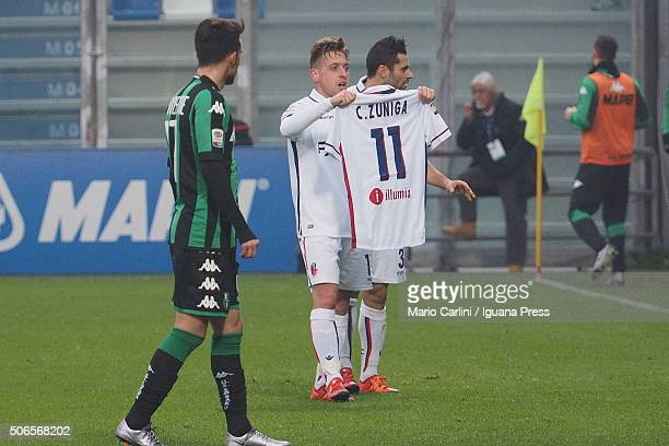 Emanuele Giaccherini of Bologna FC celebrates showing the jersey of his teamate Camilo Zuniga whose father suddenly died on yesterday after scoring...