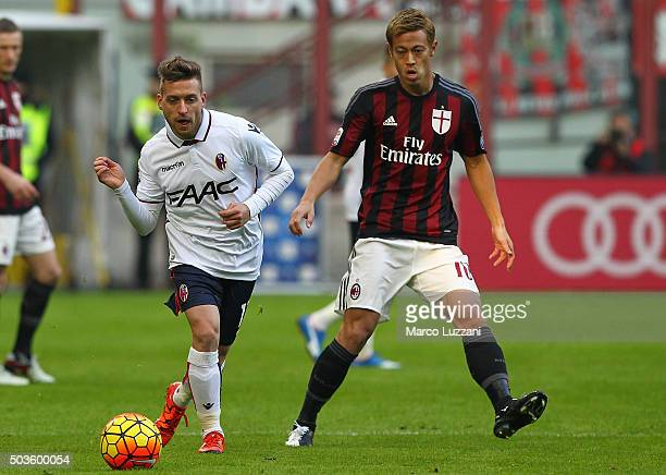 Emanuele Giaccherini of Bologna FC is challenged by Keisuke Honda of AC Milan during the Serie A match between AC Milan and Bologna FC at Stadio...
