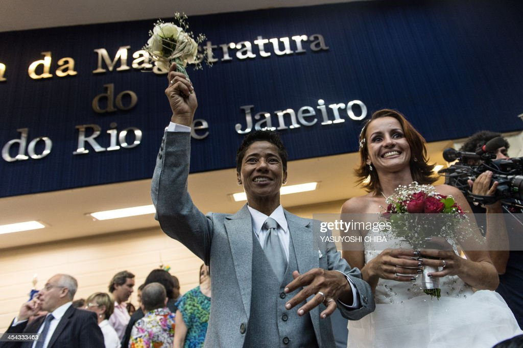 Emanuella Rosa (R) and Romilda Celina throw the bouquet after their wedding ceremony at the Court of Justice of the State of Rio de Janeiro in Rio de Janeiro, Brazil, on December 8, 2013. 130 gay couples are getting married in the first massive wedding ceremony since the first gay marriage in Rio de Janeiro in 2011. AFP PHOTO / YASUYOSHI CHIBA