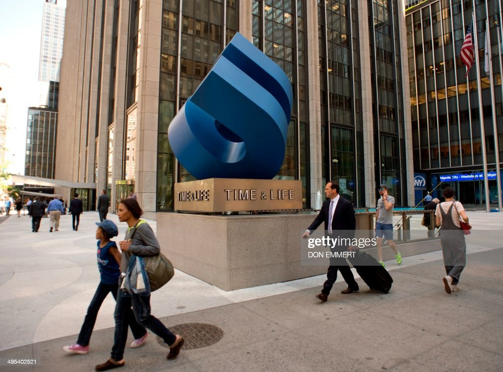 People walk past the Time Life Building on the Avenue of the Americas June 2 2014 in New York Time Inc is getting a fresh start with its upcoming...