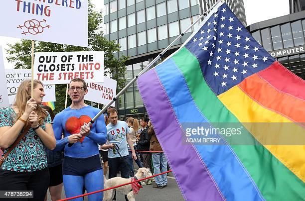 US embassy employee Tim Standaert waves a rainbow US flag as he attends the Christopher Street Day gay parade in Berlin on June 27 2015 AFP PHOTO /...