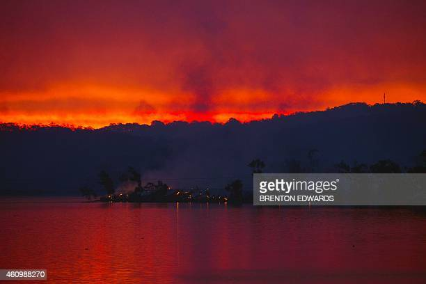 Embers glow against the smokefilled sunset near Gumeracha in the Adelaide Hills on January 3 2015 Houses were lost as an intense bushfire raged out...