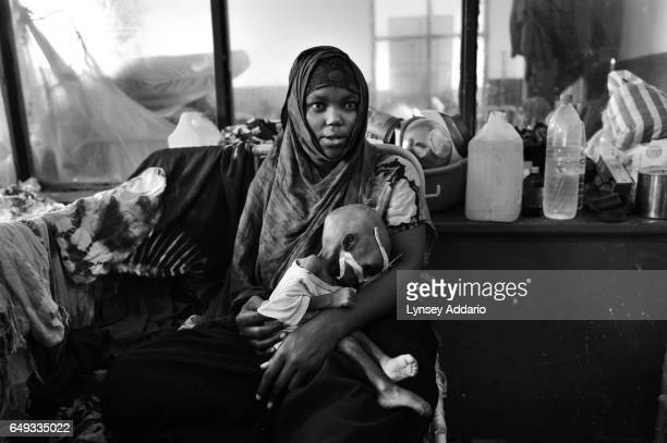 Embia Aden Hassan holds her severely malnourished daughter Fatima Ibrahim Isaac at Banadir Hospital in Mogadishu Somalia on Aug 25 2011
