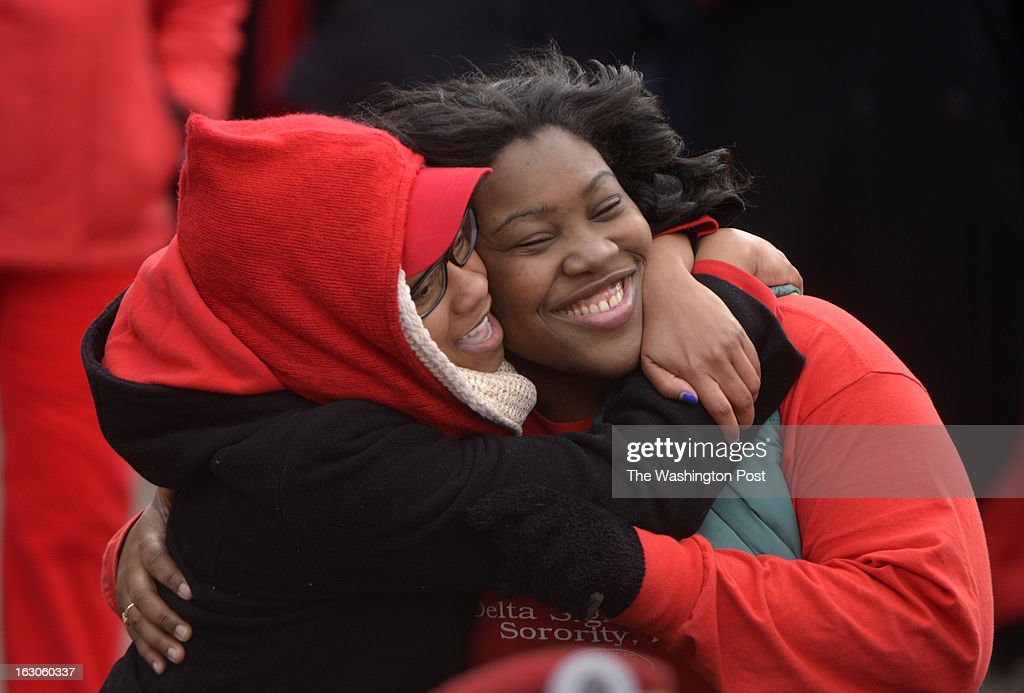 Embraced by the sisterhood of their sorority Delta Sigma Theta Sorority, Inc Jamille Harvey (left) of Daytona, Florida and Dayna Kent of Jacksonville, Florida join thousands of Deltas who retraced the footsteps of their founders in Washington, D.C. on March 03, 2013. They all gathered on the West Front of the United States Capitol and then marched past the White House and finally ended their march on the grounds of the Washington Monument. Members of Delta Sigma Theta Sorority, Inc., the single largest predominantly African-American women's organization in the country, retraced the footsteps of their founders who participated in the Women's Suffrage March of 1913. Thousands of the Sorority's members accompanied by other invited organizations, to commemorate the 100th anniversary of the role the 22 Founders of Delta Sigma Theta Sorority played in the 1913 Women's Suffrage March. Guided by the event's theme, 'Tracing the Footsteps of our Founders,' members of the Sorority will follow the symbolic route down Pennsylvania Avenue, and assembled on the grounds of the Washington Monument.