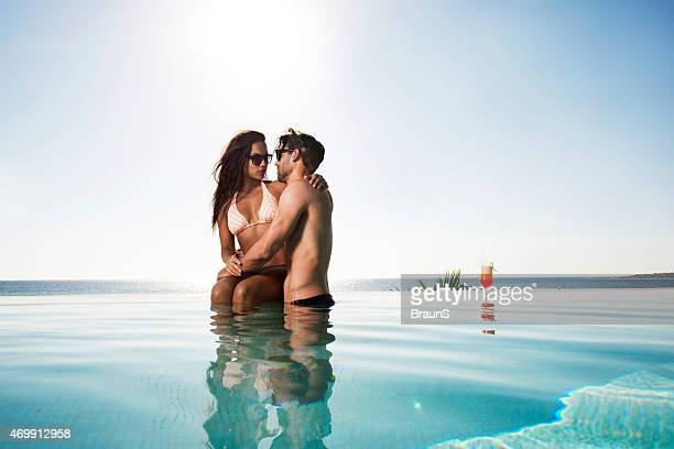 Embraced couple flirting at swimming pool in summer.