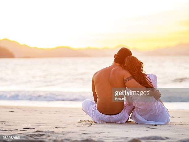 Embraced couple on the beach at sunset.