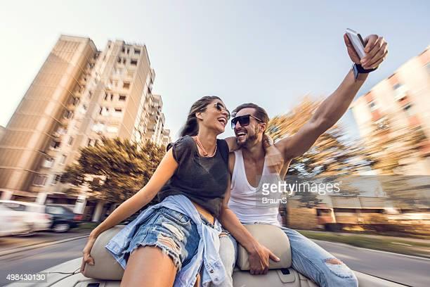 Bercée couple prenant un selfie avec téléphone portable en cabriolet.
