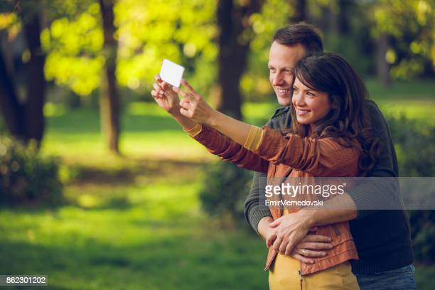 Embraced couple taking Selfie in an autumn park