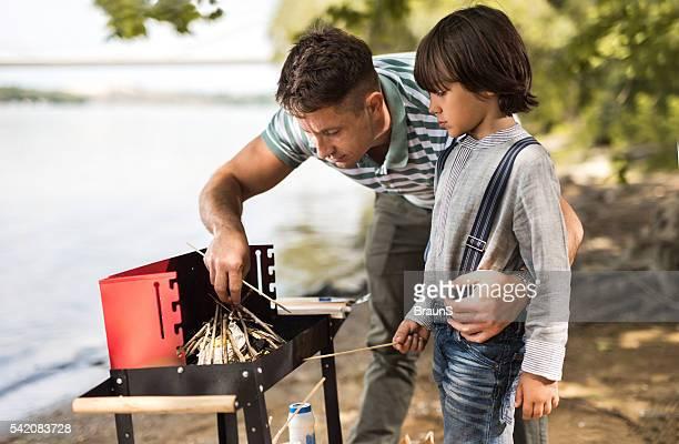 Selbstverständlich Vater und Sohn die Zubereitung von Brennholz für ein barbecue.