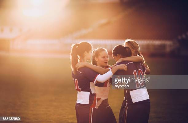 Embraced female soccer players celebrating on a playing field at sunset.